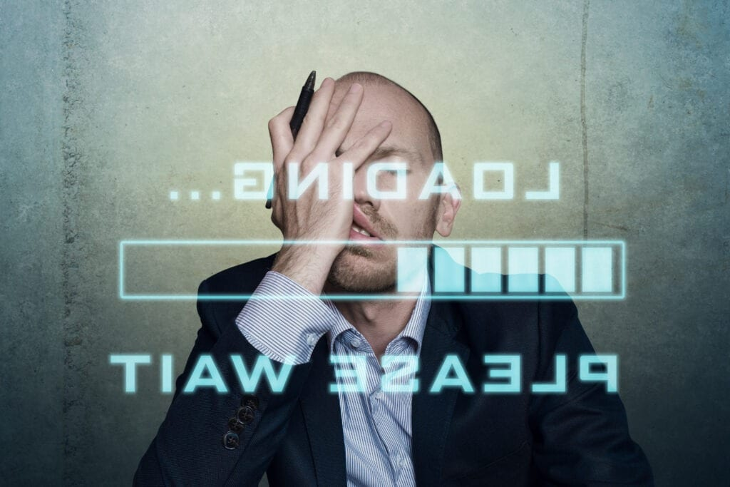 businessman or office worker waits bored and long on his slow computer or internet connection, displaying a loading bar and a messag